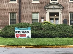"""a sign in front of a brick building reads """"Heroes Work Here"""""""