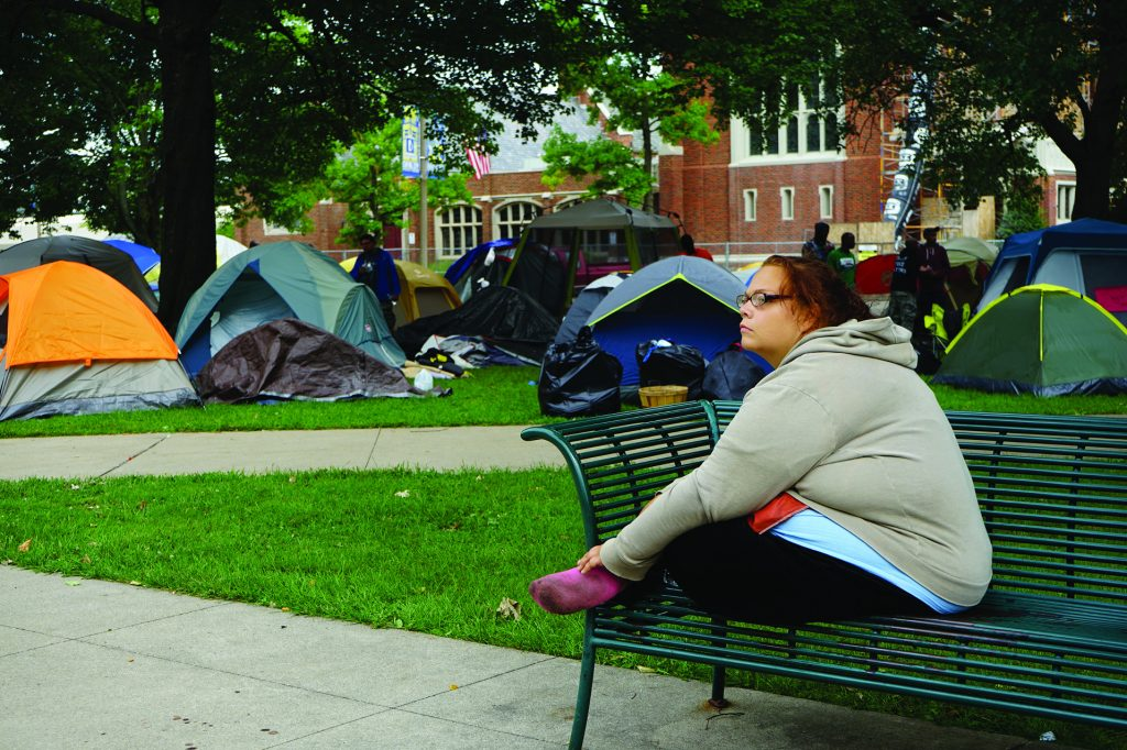 A woman sits on a park bench near a group of tents.