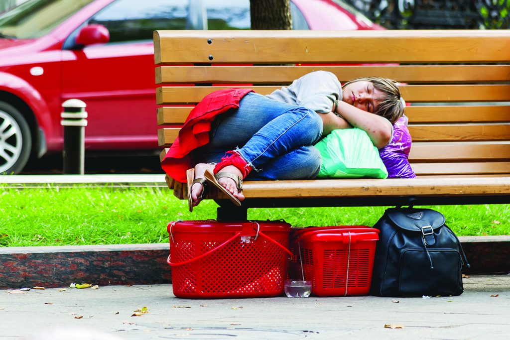 A teenage girl sleeps curled up on a park bench surrounded by her bags.