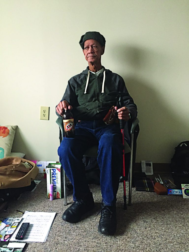 Joseph, a formerly homeless man, sits in a chair in his apartment.