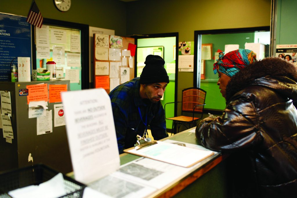 A man talks to a woman from behind the counter at Ministry With Community, a Kalamazoo homeless shelter.