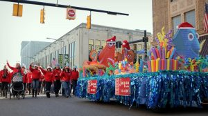 A group of people in a parade next to a holiday-themed float