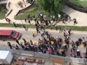 A birds-eye view of a group of people fighting, many of them holding U.S. flags