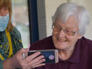 a woman in a mask shows an elderly woman photos on her phone