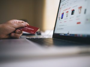 a hand holds a credit card next to a laptop while shopping online