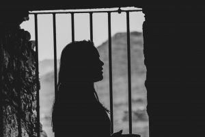 a silhouette of a woman behind the bars of a jail cell
