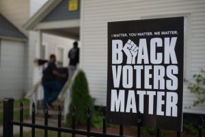 "a sign reads ""Black Voters Matter"""