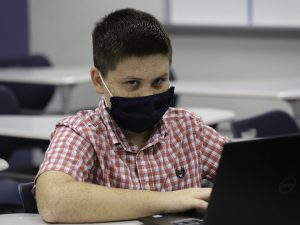 a boy in a face mask sits at a school desk and glares at the camera