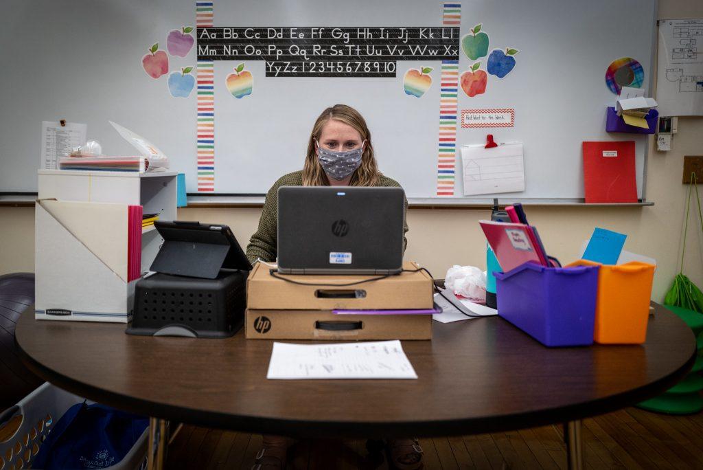 a man in a face mask teaches a class online