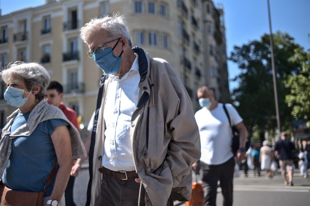 an elderly couple wearing face masks