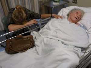 an elderly woman lays in a hospital bed