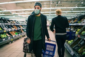 a man in a grocery store wearing a face mask