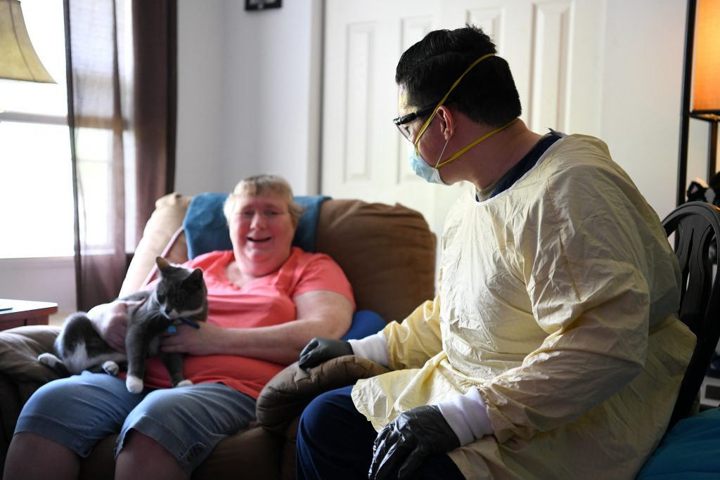 a woman sits with a man in full protective gear