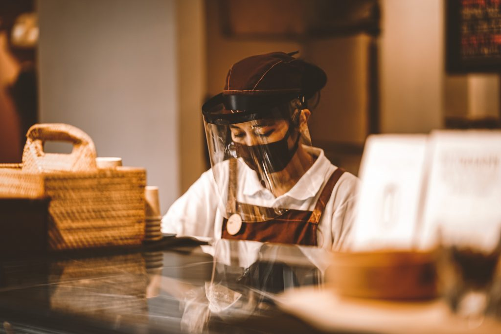 a woman in a face mask and face shield behind the counter at a restaurant