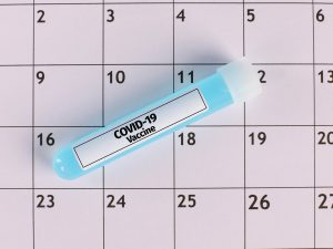 """a tube with """"COVID-19 vaccine"""" written on it in front of a calendar"""
