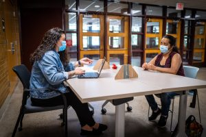 two women with face masks sit across a desk from each other