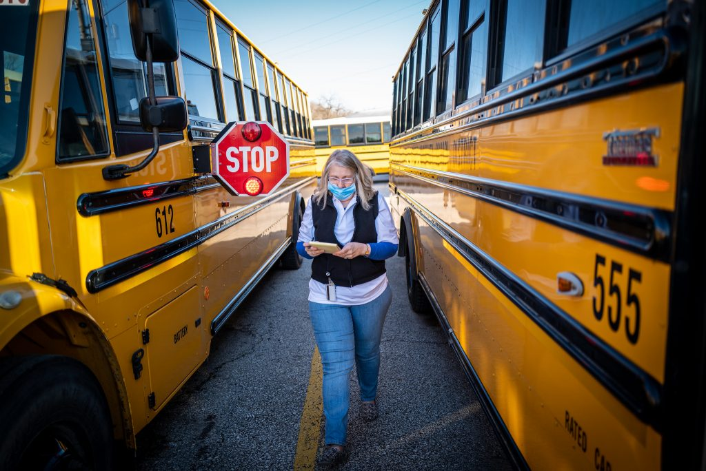 a woman in a face mask walks between two school buses