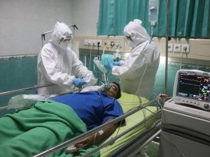 two medical workers in full PPE treat a COVID patient
