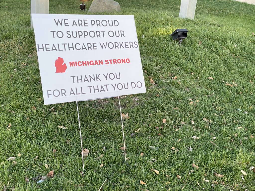 "a yard sign reads ""we support our healthcare workers. Michigan strong."""