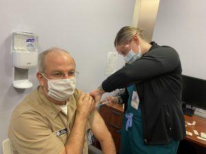 a man receives a flu vaccine in his arm by a nurse