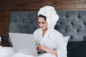 a woman with her hair wrapped in a towel working on a laptop