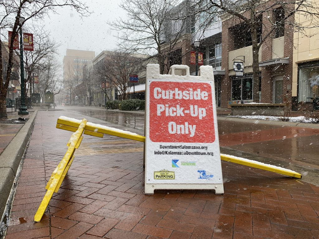 """a placard outside a restaurant reads """"curbside pickup only"""""""