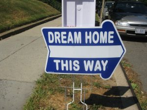 """a sign reads """"dream home this way"""""""