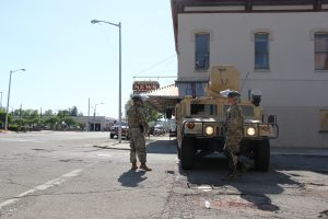 Soldiers stand in front of military vehicle in downtown Kalamazoo.