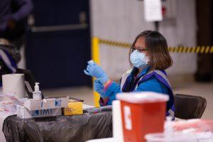 a woman in scrubs prepares a vaccine