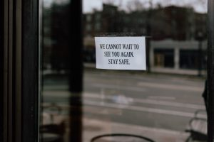 "a sign in a window reads ""We cannot wait to see you again. Stay safe."""