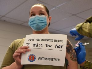 """a woman receives a COVID-19 vaccine while holding a sign saying """"I'm getting vaccinated because I miss the bar"""""""