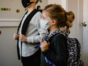 Two children with backpacks wearing face masks
