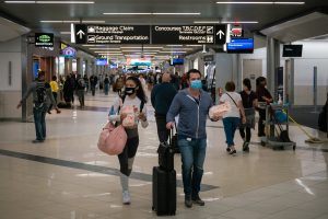 masked travelers in an airport terminal