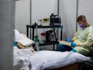 A medical worker monitors a COVID-19 patient
