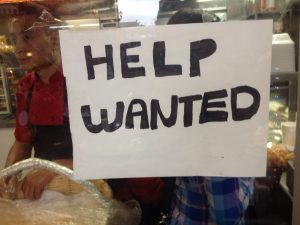 a help wanted sign in a restaurant window