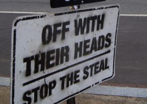 "a sign reads ""Off with their heads. Stop the steal."""