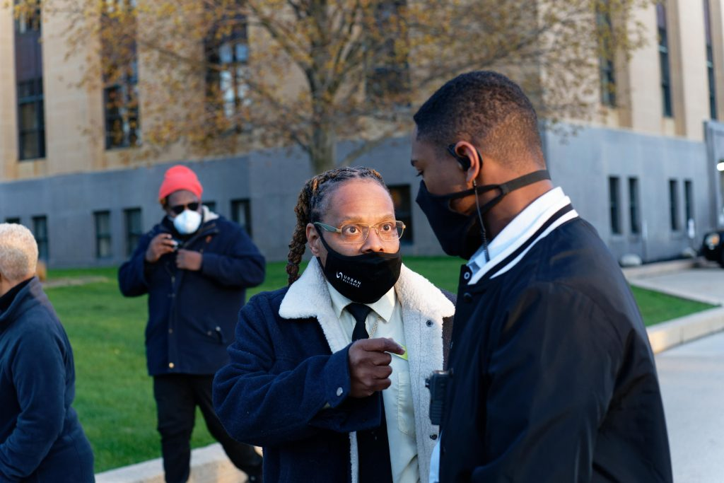 Michael Wilder (left), coordinator at Group Violence Intervention, speaks with speaks with Kalamazoo Public Safety Officer Eric Epps. (GABRIEL GIRON/NowKalamazoo)