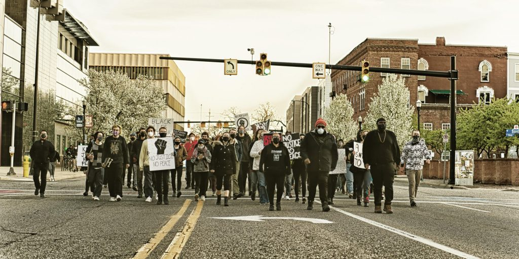 a crowd of protesters marching in downtown Kalamazoo