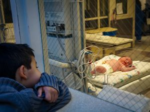 A young boy watches a baby in a hospital bed