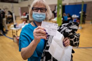 a woman shows off her COVID-19 vaccination card