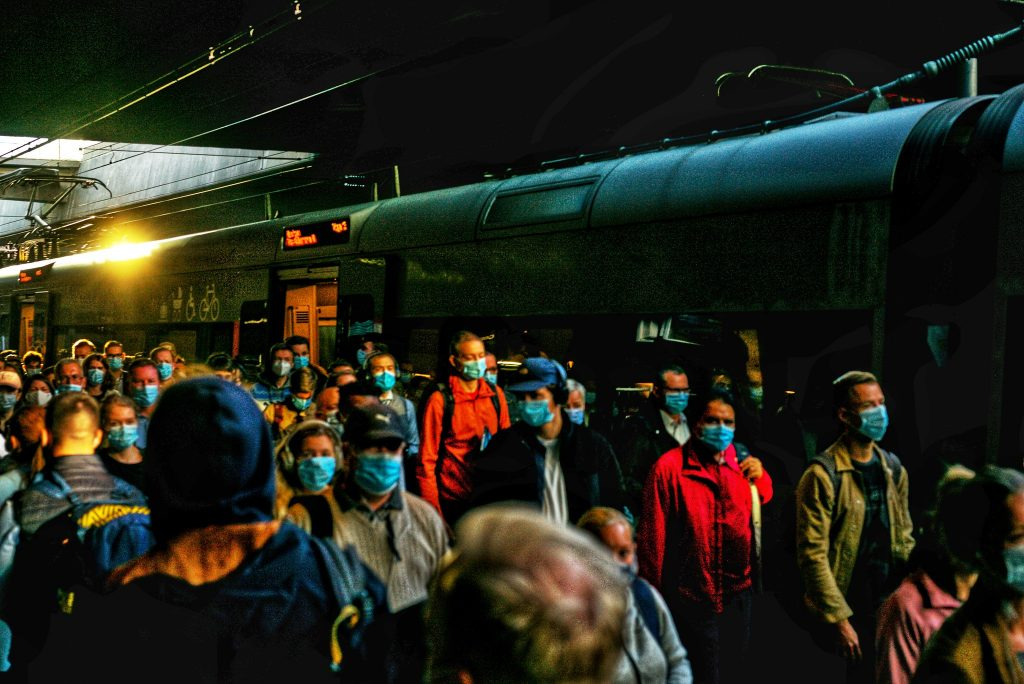 a crowd of people wearing masks at a train station