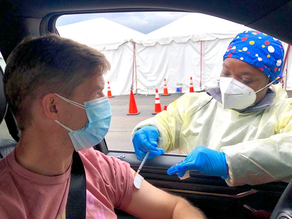 A man in a car receives a COVID-19 vaccine