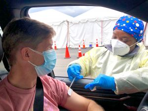 A man in a car receives a COVID-19 vaccine