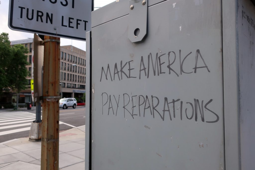"graffiti that says ""Make America pay reparations"""