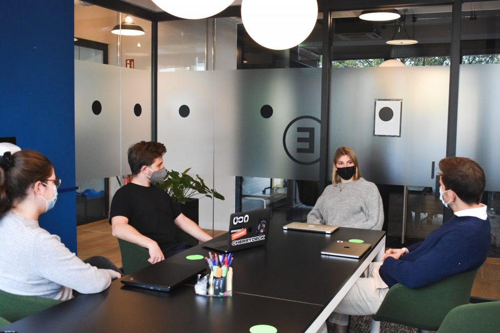 a group of young people wearing masks in a meeting room