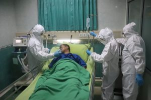 Medical workers in protective gear surround a COVID-19 patient in a hospital bed.