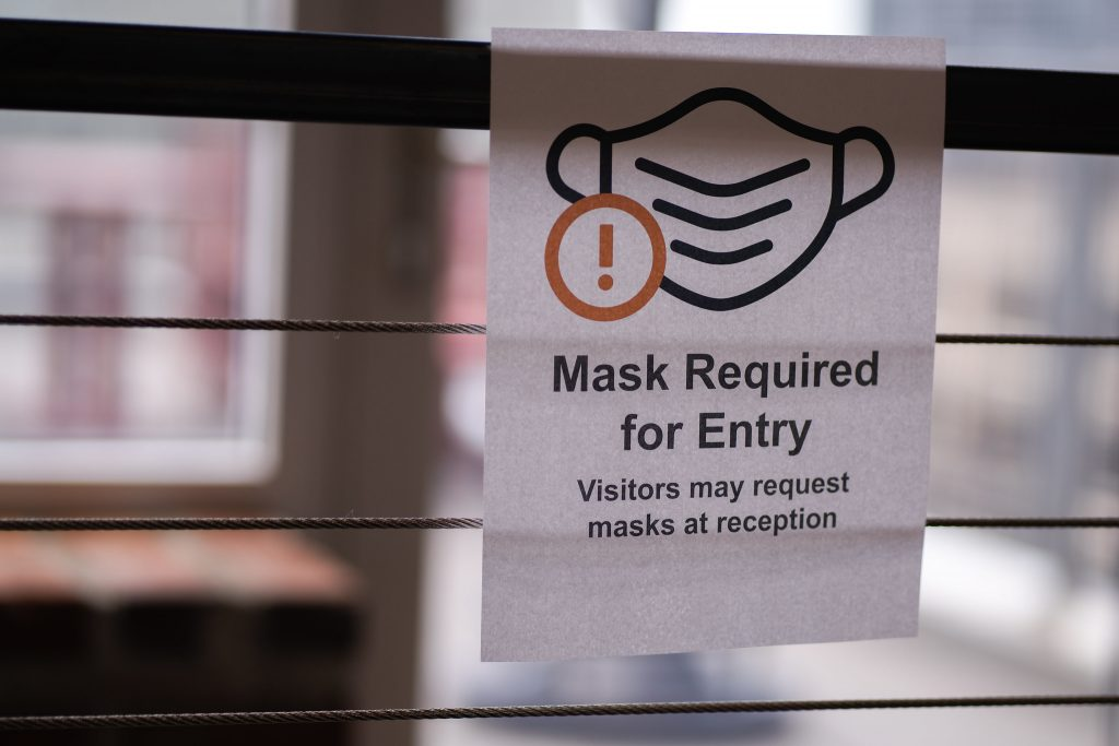 """A sign on a gate reads """"Mask required for entry"""""""