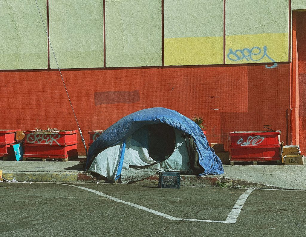 a homeless person's tent set up on a city sidewalk