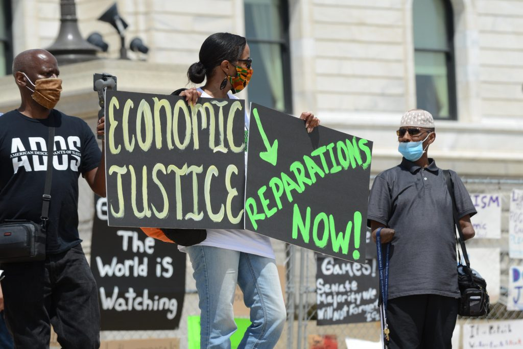 """A Black woman holds signs reading """"Economic justice"""" and """"Reparations now!"""""""
