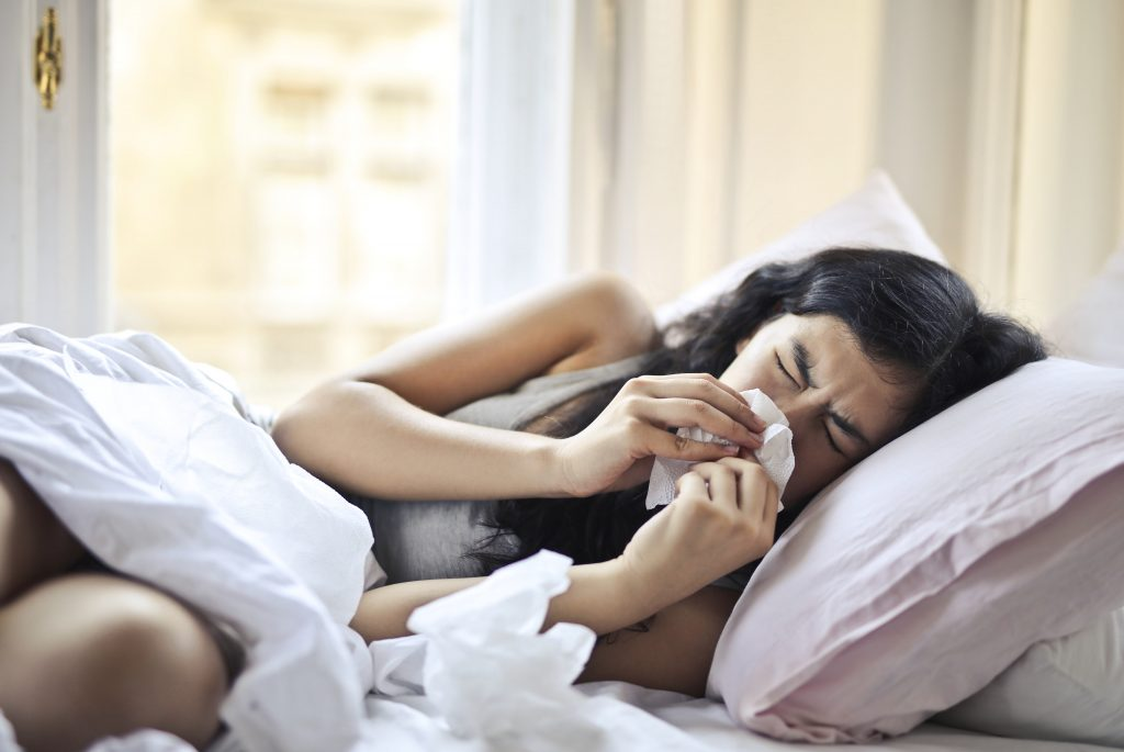 A woman lying in bed while blowing her nose